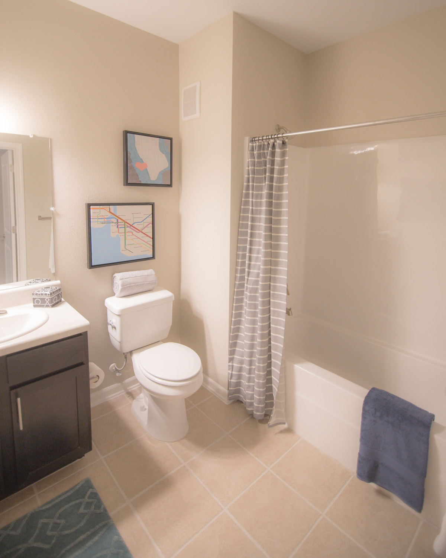 Bathroom at Bridge at Cameron with tub shower, tile flooring, and dark brown vanity