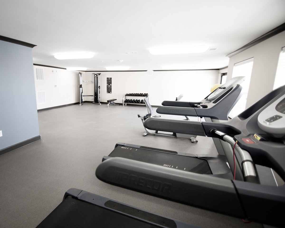 Fitness Center at Bridge at Cameron with three treadmills, free weights, and a cable machine