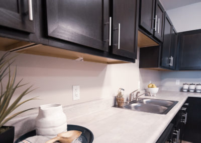 Kitchen area at Bridge at Cameron with dark brown cabinets, hard-surface countertops, and a dual-sided sink.