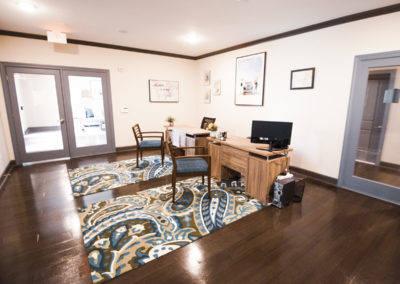 Leasing office at our Northeast Austin apartments with two wood desks and two patterned area rugs on top of hardwood floors