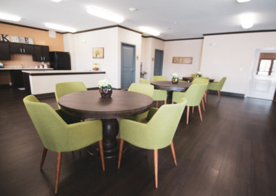 Community room with 3 brown tables each surrounded by green chairs and a kitchen prep area