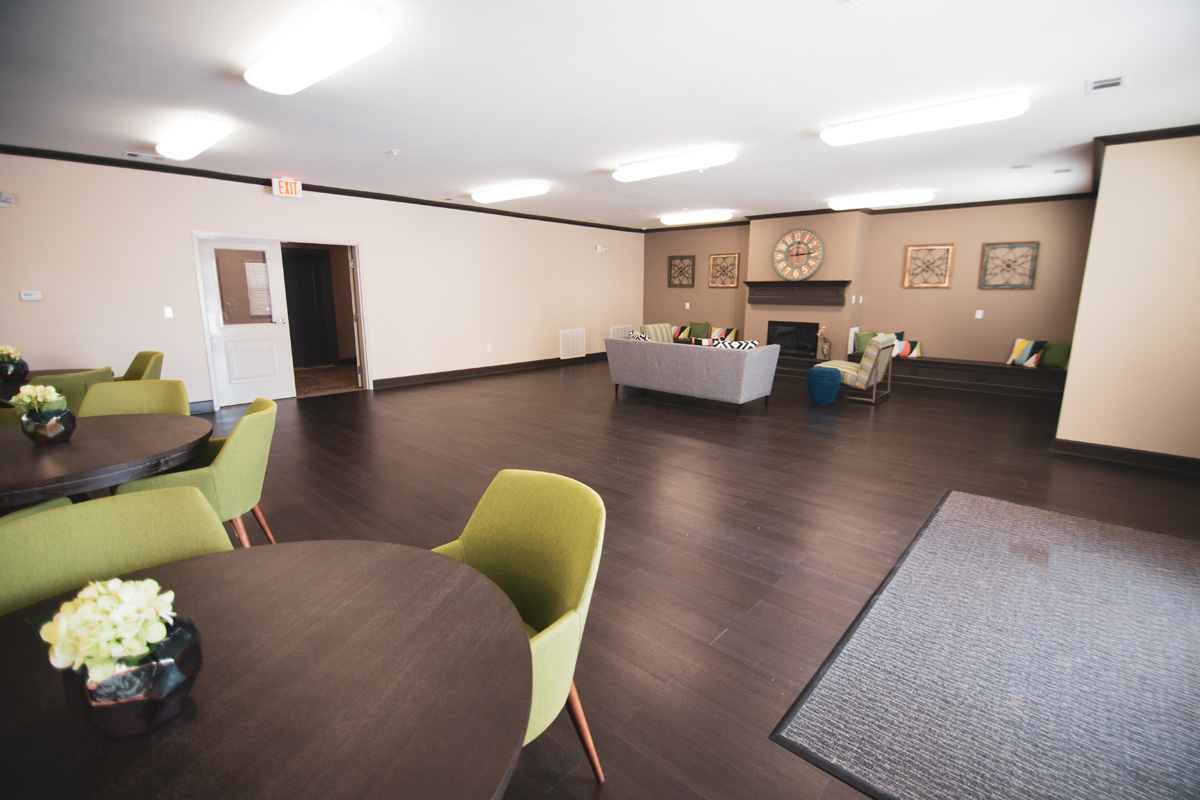 Bridge at Cameron clubhouse with hardwood flooring, a grey couch, and two striped lounge chairs surrounding a fireplace