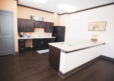Bridge at Cameron clubhouse kitchen prep area with dark brown cabinets, a sink, and black refrigerator