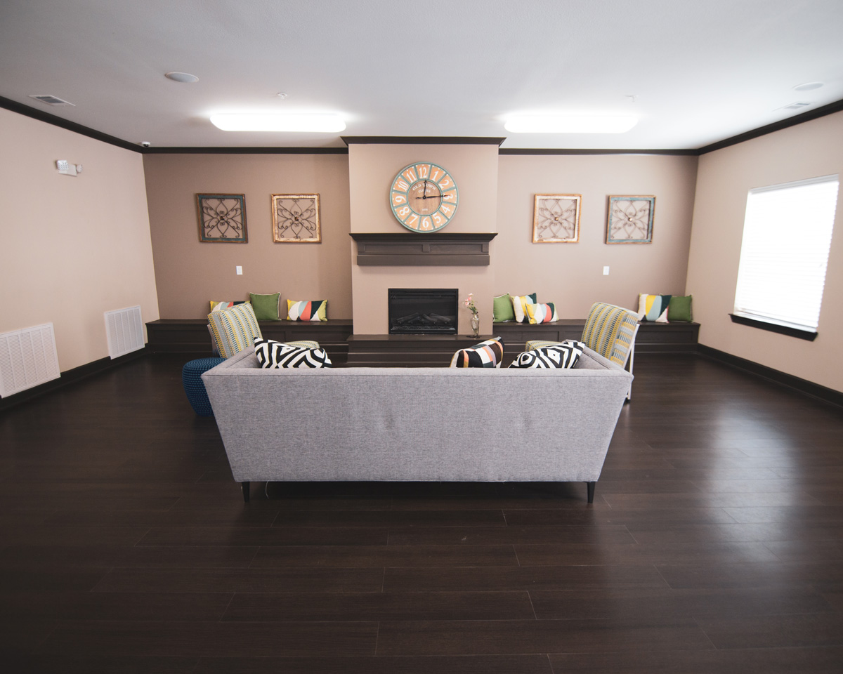 Clubhouse room at Bridge at Cameron with a grey couch and two striped green chairs in front of a fireplace