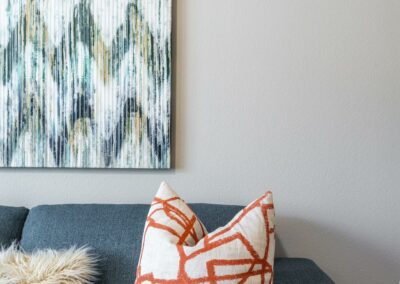Modern blue couch with an orange patterned throw pillow on it and a piece of wall art above it