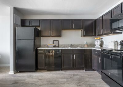 Bridge at Cameron Kitchen with Dark Cabinets, Black Appliances, and Light Faux Hardwood Style Flooring